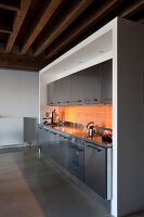 Stainless steel kitchen counter with orange wall tiles in loft apartment with rustic, wood-beamed ceiling