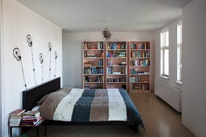 Sleeping area with designer wall lamps and bookcase