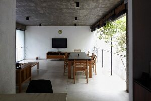 Dining table in open-plan interior with concrete ceiling