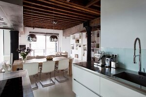 View from kitchen to dining area below mirrored spherical lamps hung from rustic wooden ceiling in loft apartment