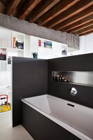 Bathtub screened by black partition wall with integrated shelf and white partition shelving in background in loft apartment