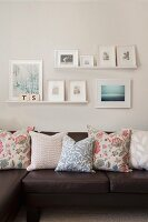 Floral scatter cushions on dark brown leather sofa and gallery of pictures in delicate shades on wall