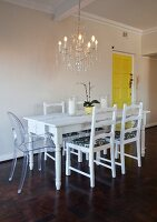 White dining table, refurbished second-hand chairs and Ghost chair below chandelier