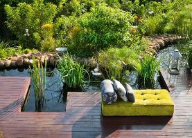 Yellow velvet cushion lounger with grey scatter cushions on wooden deck next to idyllic pool with pebbly shore and reeds