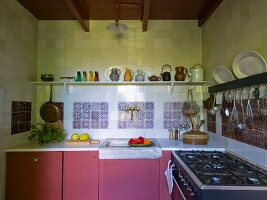 Kitchen counter with dusky-pink base units below shelf of jugs on tiled wall