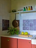 Pot of herbs and pears on worksurface above base units painted dusky pink