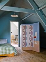 Painted screen next to bed and open door with view of chairs in adjoining room in converted attic with wood panelling painted blue-grey