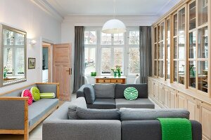Elegant library with grey sofas in pleasant period apartment