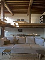 A light upholstered sofa in a rustic living area with a gallery