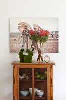 Artistic photo above pair of rabbit ornaments. vase of proteas and retro alarm clock on top of small glass-fronted cabinet