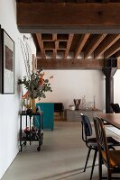 Retro chairs in loft-style interior with rustic wood-beamed ceiling and black metal column in background