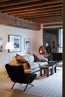 Black retro armchair and sofa around rustic coffee tables in loft-style apartment with wood-beamed ceiling