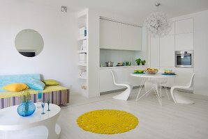 Lounge area, dining area and fitted kitchen in white, open-plan interior with round, yellow rug on white floor providing a splash of colour