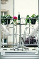 Stainless steel outdoor chairs at bistro table on balcony
