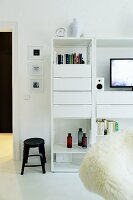 Black stool next to white shelves with drawer module