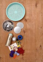 Materials for crafting wall decoration; old colander, colourful yarn, candle holder, glue