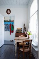 Dining table for two below window in rustic interior with vintage musical instruments in background