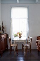 Simple dining set for two below window with curtain next to musical instruments in rustic interior
