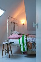 Vintage metal bed, rustic wooden stool and simple sconce lamp next to sloping ceiling section