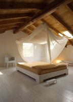 Free-standing double bed with pale painted wooden frame, translucent fabric canopy hung from wooden ceiling in open-plan attic room