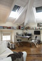 Desk and office chairs in modern, renovated attic with rustic wooden floor