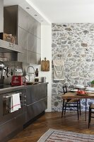 Kitchen with stainless steel fronts, stone wall and dining set
