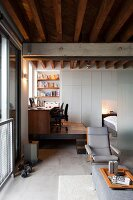 Desk, office chair and bookcase on corner platform behind lounge area