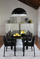 Melone pendant lamp in black and white above glossy black dining area on pale rug