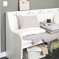 White, rustic bench with bird motifs, scatter cushions and lambskin rug against grey-painted wall