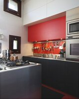 Corner of open-plan kitchen - island and counter with black fronts, spotlights recessed in red component fitted in niche