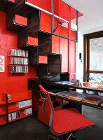 Red study - office chair and desk next to metal samba staircase on red wall