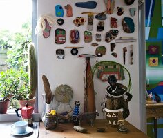 Collection of painted stones and driftwood on wall above artistic ornaments on kitchen worksurface