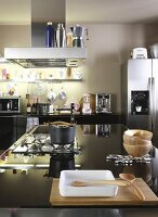 Island counter with gas hob in black worksurface; kitchen counter with base units and stainless steel cooker in background