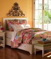 Bedroom with yellow walls, white bed and floral bed linen next to French doors overlooking garden