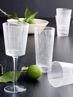Wine and water glasses with etched pattern and limes on black tabletop