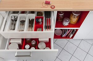 A view into open drawers in a kitchen unit with red and white cutlery and storage jar dividers