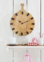 A homemade clock made from a round chopping board with dominos as numbers