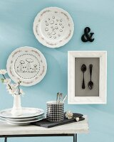 Wall decoration for the kitchen with painted plates and framed black spoons behind glass