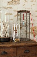 Table lamp with wire mesh lampshade next to objects under glass domes