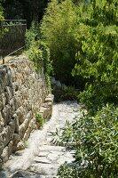 Gepflasterter Weg im Hang mit Abfangung durch seitliche Natursteinmauer in mediterranem Garten