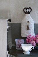 Nostalgische Kaffeetasse und Windlicht mit floralem Muster auf Nachttisch, darüber Wandleuchte
