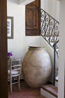 Altes Tongefäss für Oliven in Nische vor gewendelter Landhaustreppe mit schmiedeeisernem Geländer