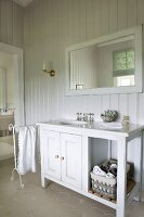 White-painted, wooden washstand cabinet in country-house bathroom with wood-panelled walls painted pale grey