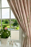 View through window past gathered curtain and potted geranium to grand, landscaped gardens