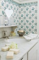 Traditional, floral tiles behind washstand with classic marble top and old tap fitting