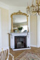 Mirror with magnificent gilt frame above open fireplace in elegant interior with crystal chandelier