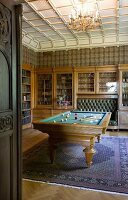 Old-fashioned room for convivial gatherings with glass-fronted cabinets, integrated leather bench, library and billiard table