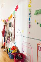 Colourful baskets of children's accessories, paper garlands and washi-tape pictures on wall of child's bedroom