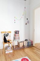 Folders in wooden boxes on floor and decorative hat boxes below colourful garland on wall