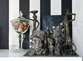 Collection of metal ethnic figurines and glass jar against wallpaper with wide black and white stripes